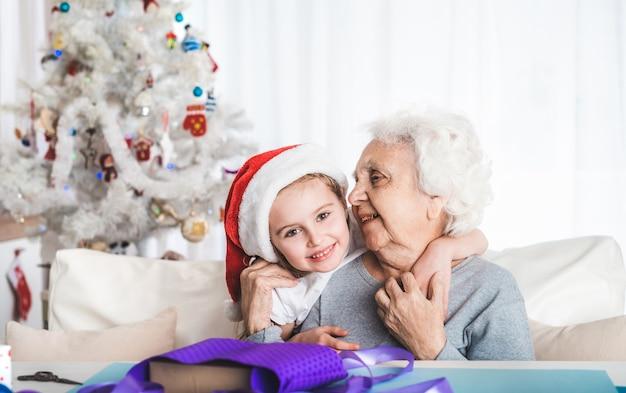 サンタの帽子をかぶった孫娘がクリスマスにおばあちゃんと抱き合って座っています