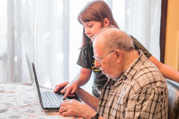 Внучка помогает дедушке пользоваться компьютером