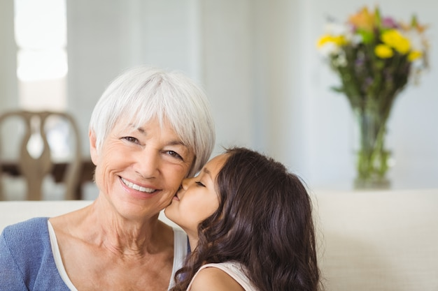 Granddaughter kissing grandmother on cheek in living room