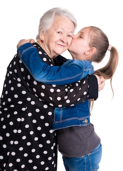 Granddaughter kissing her grandmother on white wall