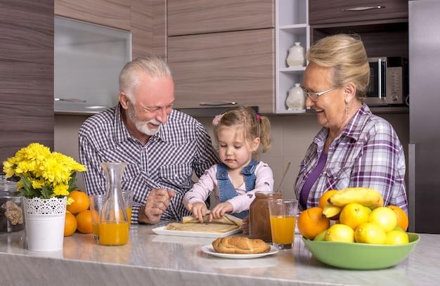 Внучка играет с бабушкой и дедушкой на кухне