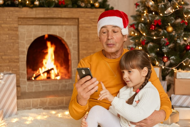 Granddaughter sitting with her grandfather on floor on soft carpet near fireplace and decorated fir tree