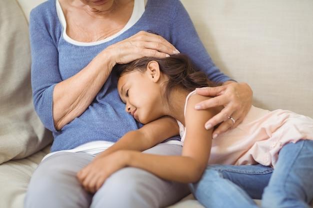 Granddaughter sleeping on grandmothers lap in living room