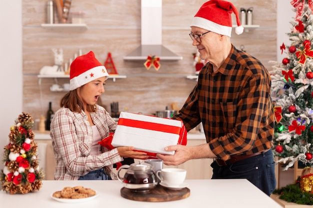 Granddaughter surprising grandfather with wrapper gift celebrating christmas holiday