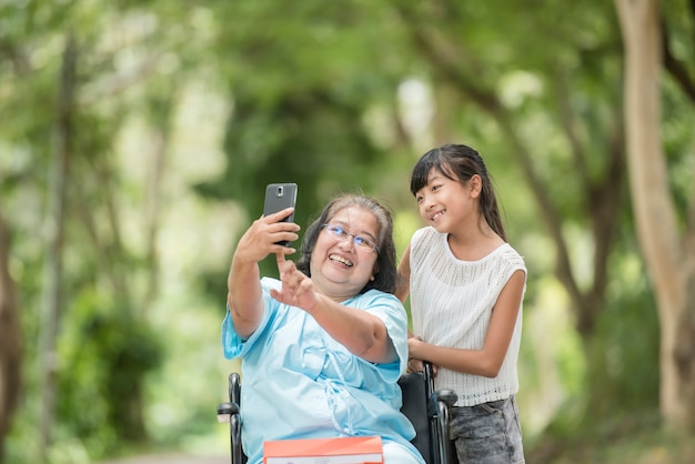 Granddaughter taking a picture with her grandmother in a wheelchair