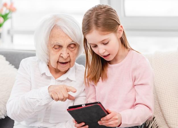 Granddaughter teaching grandmother use tablet.