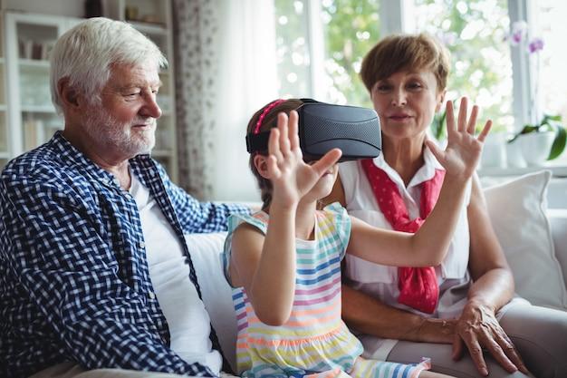 リビングルームで祖父母と仮想現実のヘッドセットを使用する孫娘