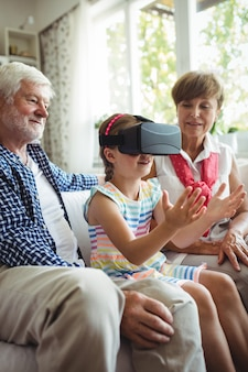 Granddaughter using virtual reality headset with her grandparents in living room