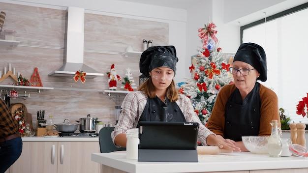 집에서 만든 진저브레드 반죽을 준비하는 태블릿 컴퓨터를 사용하여 요리 수업을 보고 있는 손녀