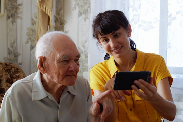 A grandfather and an adult granddaughter are sitting on the sofa and looking at their mobile phone