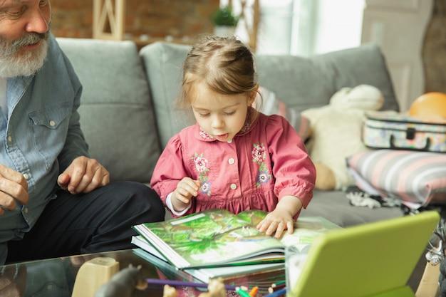 할아버지와 아이가 집에서 함께 연주. 행복, 가족, 관계, 교육 개념.