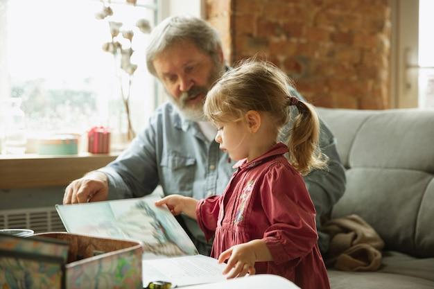 Дед и ребенок, играющие вместе дома, концепция образования семейных отношений счастья