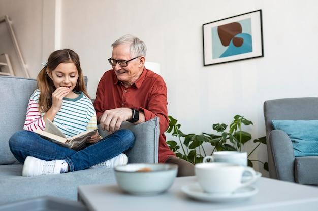 Дедушка и девочка читают вместе