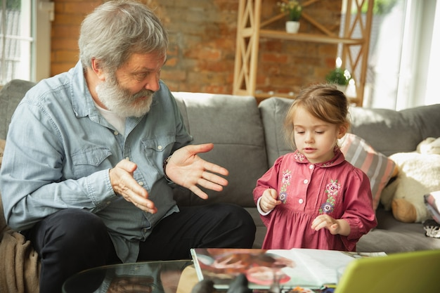 Дед и внук вместе играют дома. концепция счастья, семьи, отношений, обучения и образования. искренние эмоции и детство. читаем книги, сказки, стихи, выглядим счастливыми.