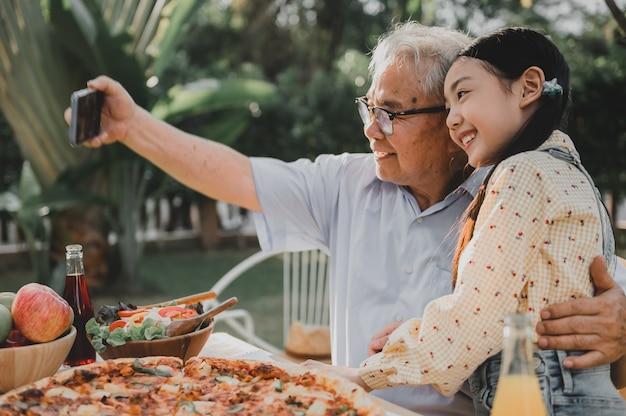 할아버지와 손녀는 집에서 정원에서 저녁을 먹고 있습니다. 여름 휴가에 가족과 함께 은퇴 연령 생활 방식.