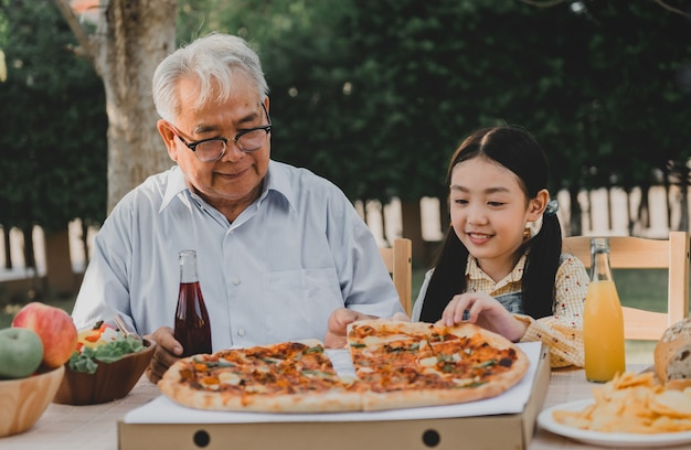 할아버지와 손녀가 집에서 정원에서 피자를 먹고 있습니다. 여름 휴가에 가족과 함께 은퇴 연령 생활 방식.