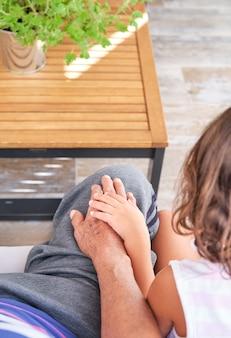 Дедушка и внучка, взявшись за руки, сидят на спине с коричневым деревянным низким столиком на заднем плане