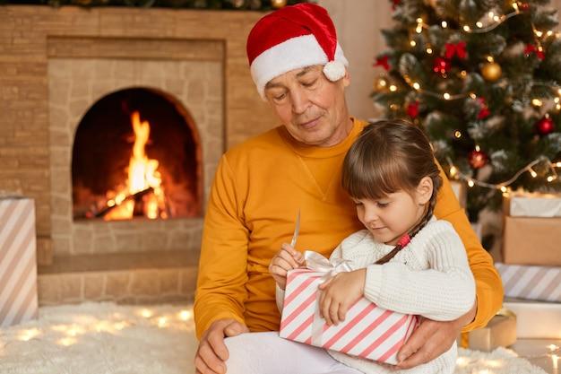 祖父と孫娘がクリスマスプレゼントを開く