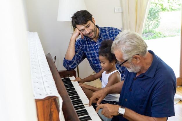 祖父と孫娘がピアノを弾きながら、父が彼らのそばに座っている家族の概念