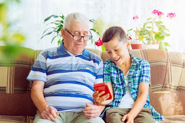 祖父と孫はソファに座って携帯電話を見ています。少年は老人に現代のスマートフォンの使い方を教えています。