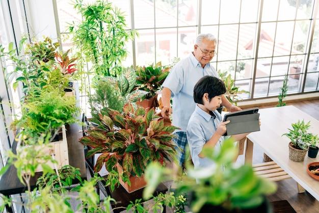 祖父と孫はタブレットで植物を売るために住んでいます