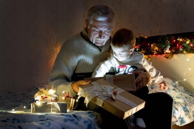花輪の光のある部屋でクリスマスプレゼントを開く祖父と孫