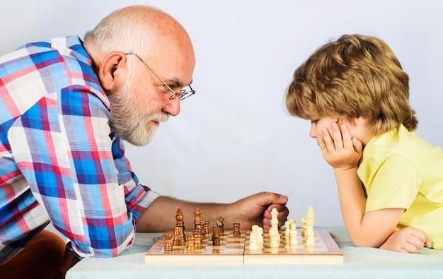 チェスをしている祖父と孫。チェスをすることを学ぶ子供。小さな男の子はチェスゲームを考えたり計画したりします。チェックメイト。