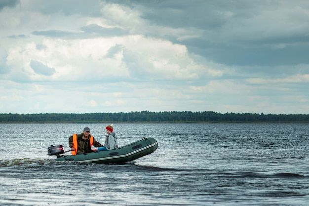 Дед и внук катаются на моторной лодке по озеру.