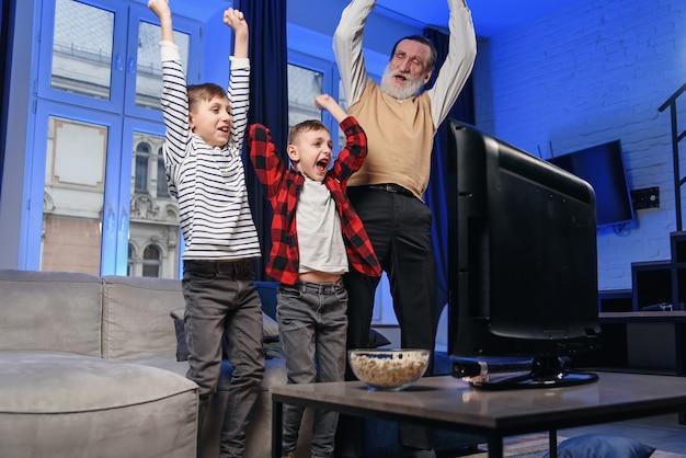 Дед и внук смотрят телевизор. дед и внук наслаждаются дома.