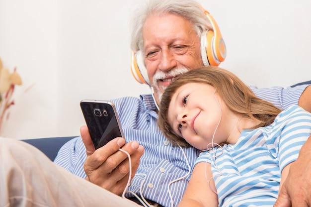 헤드폰을 든 할아버지와 손자는 소파에서 서로 포옹하는 음악을 듣습니다.