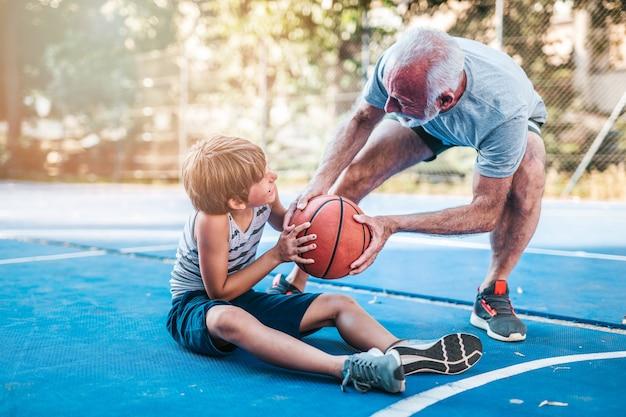 할아버지와 그의 손자가 농구 코트에서 함께 즐기고 있습니다.