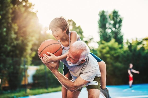 祖父と孫がバスケットボールコートで一緒に楽しんでいます。