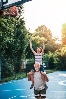 祖父と孫がバスケットボールをしている。