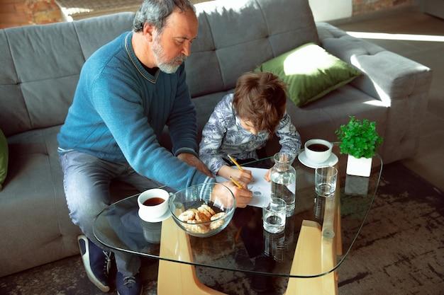 Дед и его внук проводят время в изоляции дома и веселятся