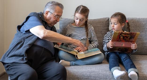Дед и его маленькие внучки рассматривают семейные фотографии в фотоальбомах.