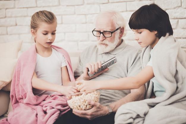 Дед и дети смотрят телевизор есть попкорн.