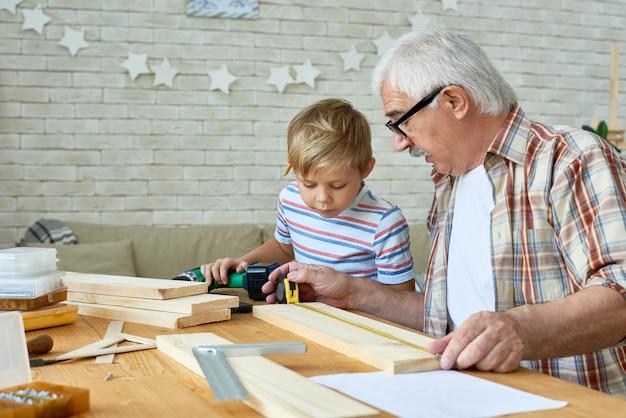 祖父と小さな男の子が一緒に木製のモデルを作る