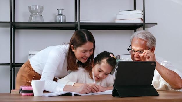 Дедушка и мать учат дочь домашнему заданию во время онлайн-учебы дома.
