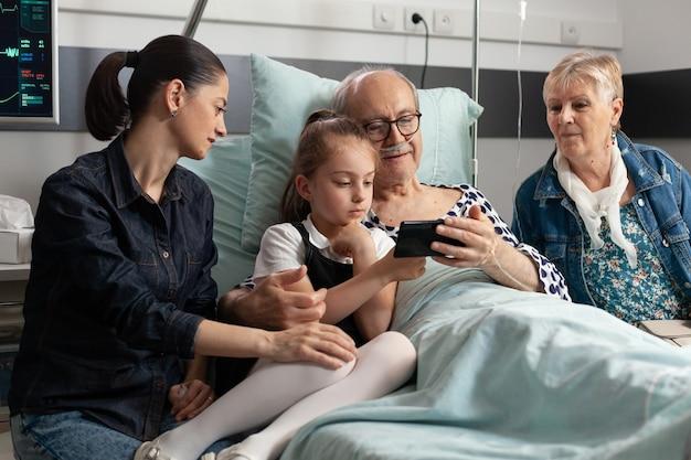 祖父は現代のスマートフォンを使用して小さな孫娘とインターネットでブラウジング