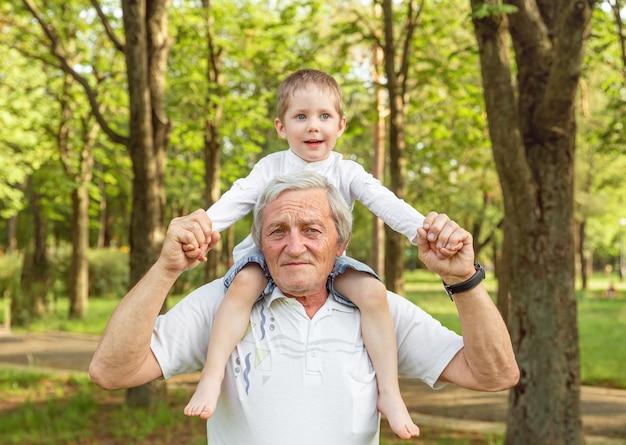 어깨에 손자를 들고 할아버지. 수석 남자와 손자