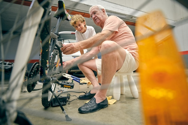 Grandfather checking tires on bicycle wheel of grandson