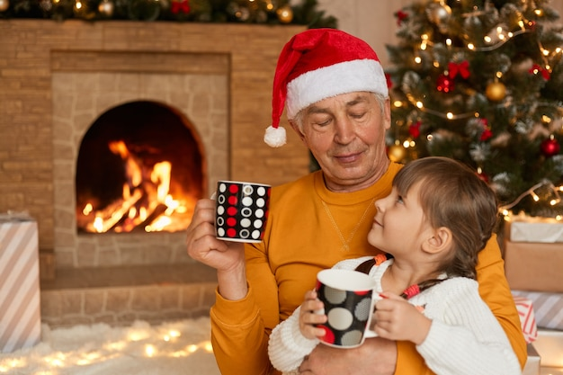 Grandfather and child girl posing together indoor near decorated xmas tree with lights, they talking, smiling and drinking hot tea, looking at each other. merry christmas and happy holidays!