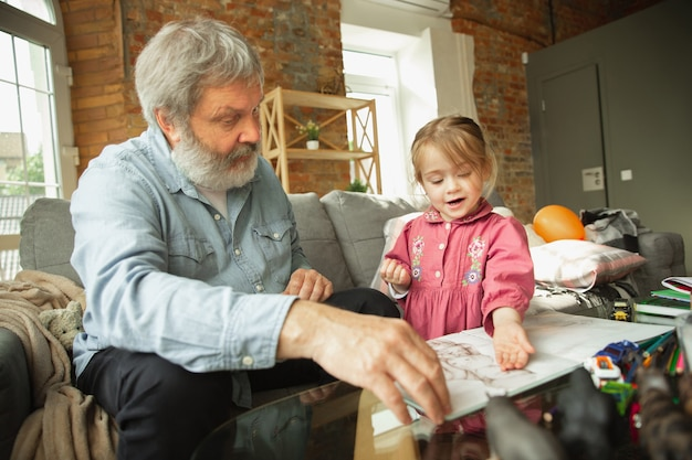Grandfather and child playing together at home happiness family relathionship education concept