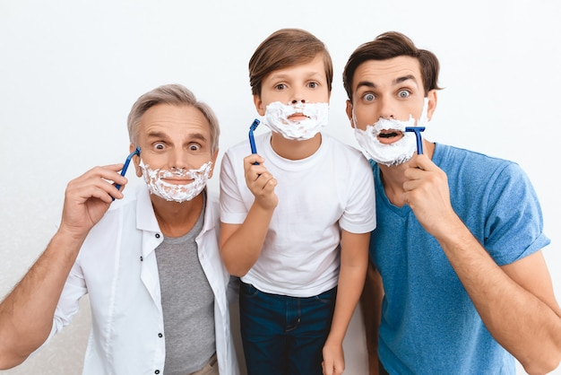 Grandfather father and a grandson. foam shaving.