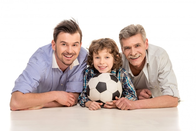 Grandfather, father and son lying on white