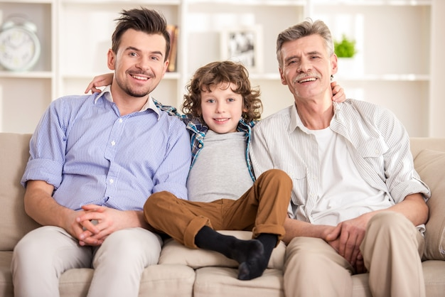 Grandfather, father and son sitting on sofa.