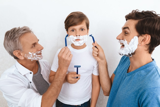 Grandfather and father and son with shaving foam on faces.