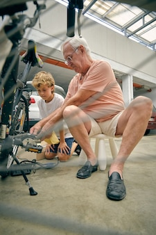 Grandfather fixing bicycle for grandson on parking lot