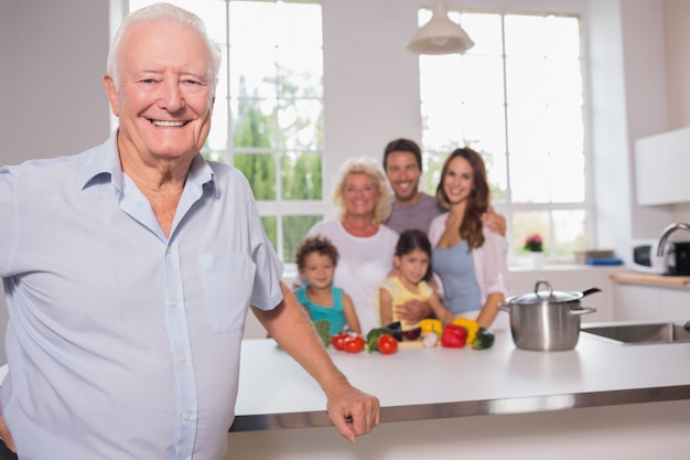Grandfather in front of his family in the kitchen