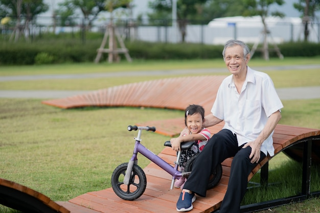 Grandfather and grandchild play and ride bike at outdoor park